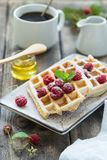 Delicious breakfast with waffles and raspberries. Delicious breakfast with waffles, fresh raspberries and coffee Royalty Free Stock Photography