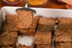 Delicious brown colored chocolate brownies lined up, square pieces as seen from above angle, metal cake cutter being Royalty Free Stock Photography