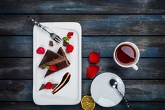Delicious brownie cake with a cup of tea rose petals and forks on a white plate. Top view. Beautiful wooden background. Stock Photography