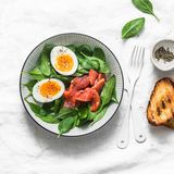 Delicious brunch - spinach, smoked salmon, soft boiled egg on a light background, top view. Healthy eating diet concept. Delicious brunch - spinach, smoked royalty free stock photography