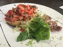 Delicious bruschetta. Bruschetta is an antipasto & x28;starter dish& x29; from Italy consisting of grilled bread rubbed with garlic and topped with olive oil and Stock Photos