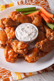 Delicious buffalo wings with sauce and celery close-up. Vertical Royalty Free Stock Image