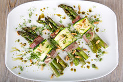 Delicious bunch of asparagus rolled with ham, zucchini, pine nut Stock Photo