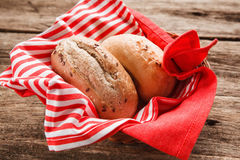 Delicious buns in basket on rustic wooden table. Two fresh bread buns in the basket on wooden table, close up view. Food background, menu photo Royalty Free Stock Photos