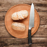 Delicious buns on wooden background, top view. Food background. Two baked bread buns served on platter with knife, on wooden table, flat lay. Bakery, lunch Stock Photo
