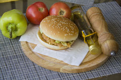 Delicious burger against fresh vegetables Royalty Free Stock Photos