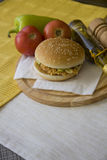 Delicious burger against fresh vegetables Royalty Free Stock Photography