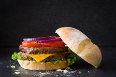 Delicious burger with cheddar cheese, tomato, lettuce and onion. Black slate background Royalty Free Stock Photo