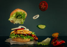 Delicious burger with flying ingredients on dark background. Delicious burger with flying tomato, cucumber and onion slice on dark background Stock Photography