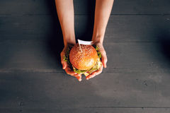 Delicious burger in hand. Stock Photo