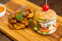 Tasty burger with meat on wooden platter Stock Photo