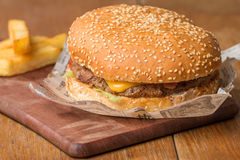Delicious burger  on paper and fries Royalty Free Stock Photos