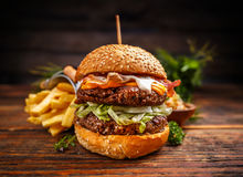 Delicious burgers with beef patty. Bacon, cheese and cabbage on rustic wooden background Stock Photo