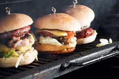 Delicious burgers with beef, tomato, cheese and lettuce. cooked on the grill assembled. heat the grill and the smoke Stock Photos