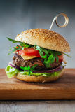 Delicious burgers with beef, tomato, cheese and lettuce. Shot on a wooden table Royalty Free Stock Images
