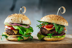 Delicious burgers with beef, tomato, cheese and lettuce. Shot on a wooden table Royalty Free Stock Image