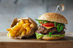 Delicious burgers with beef, tomato, cheese and lettuce. Shot on a wooden table Royalty Free Stock Photo
