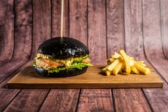 Delicious burgers of black dough with red fish on a beautiful slate board stock images
