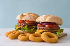 Delicious burgers with cheddar cheese, tomato, lettuce and onion. Blue background Stock Photography