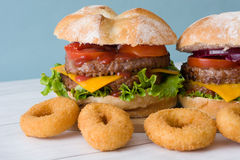 Delicious burgers with cheddar cheese, tomato, lettuce and onion. Blue background Royalty Free Stock Image