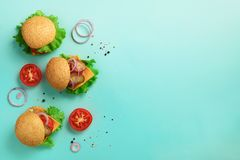 Delicious burgers, cheese, lettuce, onion, tomatoes on blue background. Close up banner. Unhealthy diet concept. Top view. Banner. With copy space stock images