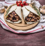 Delicious burrito with meat, beans, and vegetables on a cutting board and a napkin with cherry tomatoes garlic on wooden rusti Stock Photos