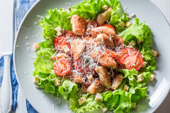 Delicious Caesar salad with chicken, cherry tomatoes and parmesan cheese Royalty Free Stock Images
