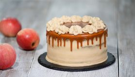 Delicious cake with apple and whipped cream filling, topped with caramel.  stock image