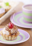 Delicious cream pastry on a plate, ready to eat. Delicious cake basket with cream and cherry on a plate Stock Photos