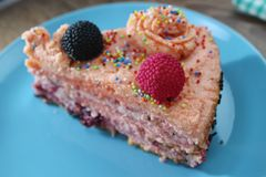 Delicious cake on a blue and white plate with chocolateTasty cake with strawberries, blackberries and colorful sprinkles on the bl. Tasty cake with strawberries stock images