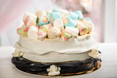 Delicious cake with cream, decorated with marshmallow, on a blurred background. Horizontal frame Royalty Free Stock Photos