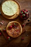 Delicious cake with fresh organic strawberries on cutting board over wooden background, close-up, selctive focus.