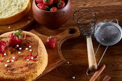 Delicious cake with fresh organic strawberries and kitchen utensils, top view, close-up, selctive focus.