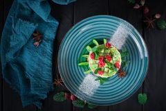 Delicious cake with fruit and mint decoration on black background.  Stock Image