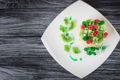 Delicious cake with fruit and mint decoration on wooden table.  Stock Photos