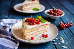 Delicious cake with mascarpone, whipped cream, red currant and almond slices. Delicious cake filled with mascarpone, whipped cream, red currant jam and decotated stock image