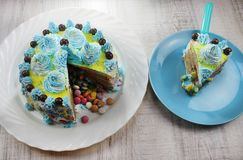 Delicious cake slice on a blue and white plate with chocolate candies royalty free stock images