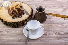 A delicious cake on wooden stump with a coffee cup, fork, tea spoon, coffee beans and bowl with sugar cubes on a wooden background.  Stock Photo