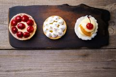 Delicious cakes. home crafted sweet desserts. Delicious assorted different mini cakes with cream and berries. home crafted sweet desserts, confectionery royalty free stock image