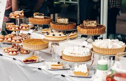 Delicious cakes and pie with whipped cream on table at street food festival. candy bar with tasty sweets, catering at wedding rec. Eption. open kitchen outdoors stock photos
