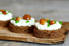 Delicious canape with soft cheese and mushrooms on a board on a wooden background Royalty Free Stock Photo