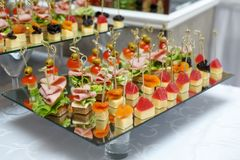 Delicious canapes with ham, cheese and fruit stock photo