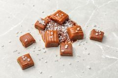 Delicious candies with salted caramel sauce. On light background Stock Photo