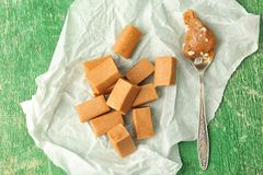 Delicious candies and salted caramel sauce in spoon. On wooden table, top view Stock Image