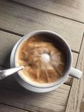 A delicious cappuccino in a Porzellan cup. Placed on a wooden table royalty free stock image