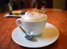 Delicious cappuccino in white cup on the wooden table Royalty Free Stock Photo