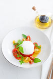Delicious caprese salad with ripe cherry tomatoes and mozzarella cheese with fresh basil leaves and olive oil. Italian Stock Images