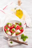 Delicious caprese salad with ripe tomatoes and mozzarella cheese with fresh basil leaves. Italian food. Royalty Free Stock Images