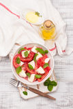 Delicious caprese salad with ripe tomatoes and mozzarella cheese with fresh basil leaves. Italian food. Stock Photos