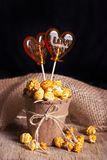 A delicious caramel popcorn in a paper cup and lollipops Royalty Free Stock Photo